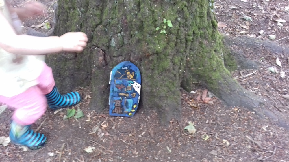 A blue painted fairy door on a tree amongst woo