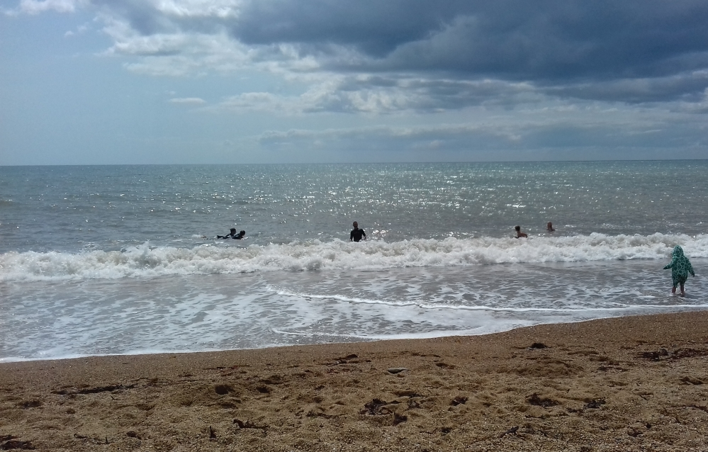 The sea and sand of Burton Bradstock with some paddlers