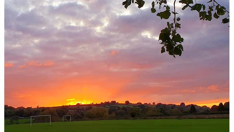A picture of the sunset over a field