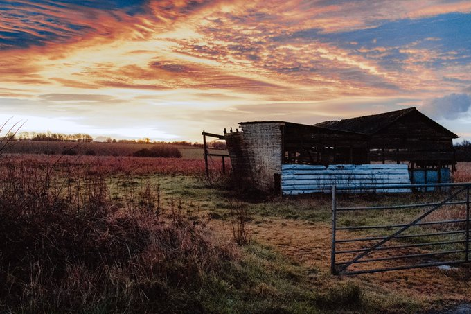 A run down barn set against a pink sky and fiels