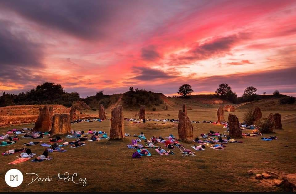 A pink sky with the stone circle at Ham Hill and yoga mats