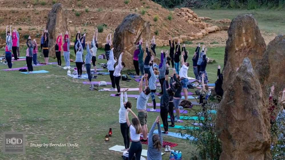 People with yoga mats in the outdoors stretching their hands to the sky