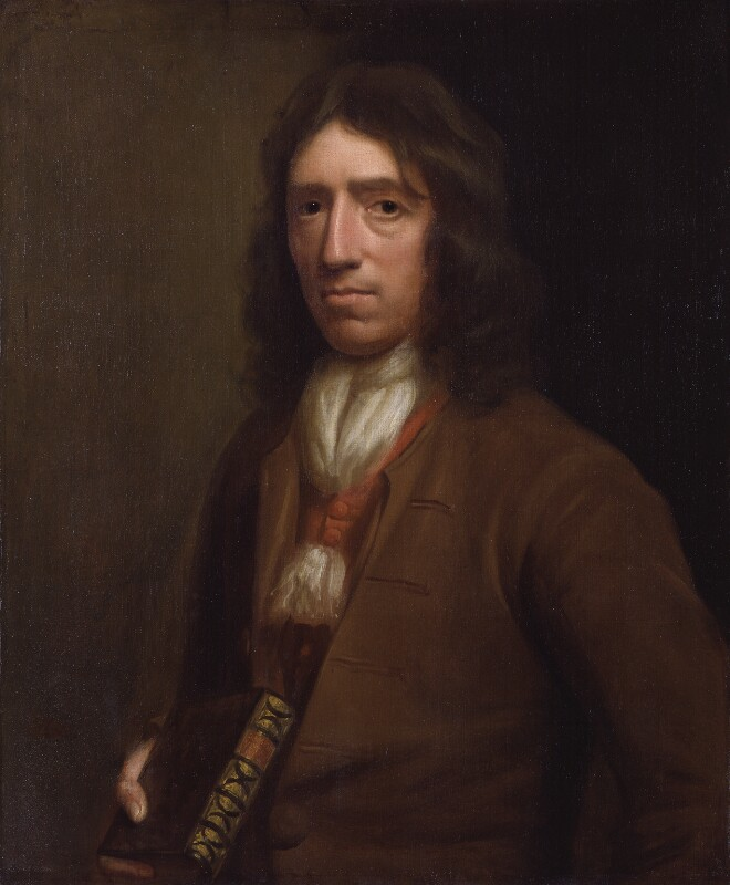 Long haired man in a brown suit clutching a book