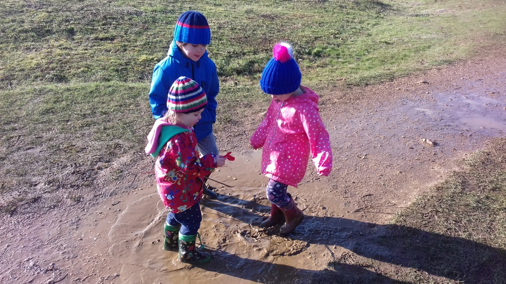 Three kids with hats and coats around a muddy puddle