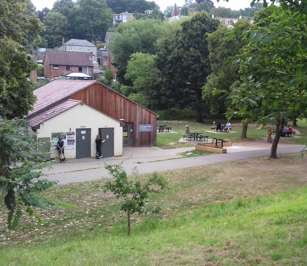 A wooden cafe structure with picnic benches outside set in woodland
