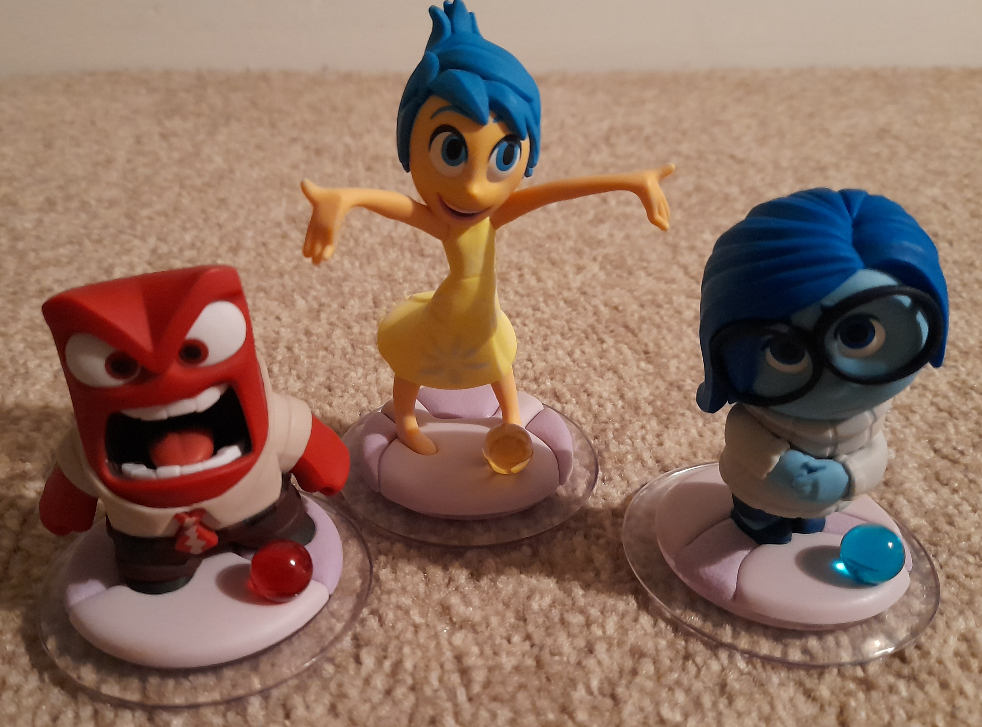 Three characters red is Anger, yellow is Joy and blue is Sadness