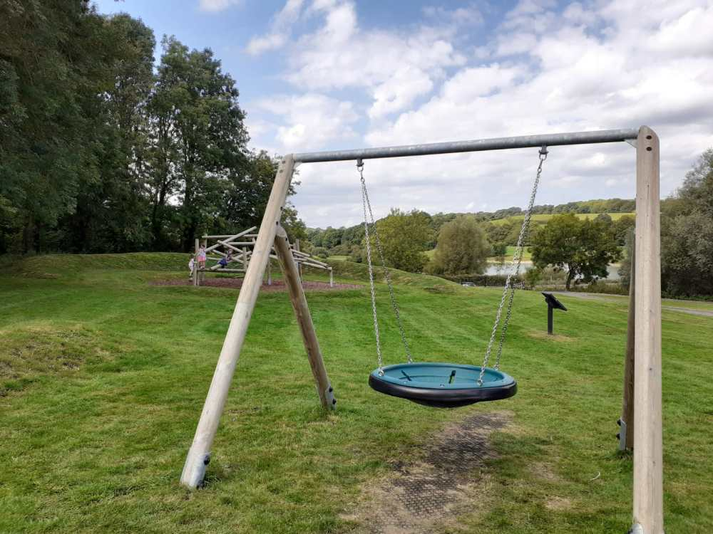 A large round swing and wooden climbing frame