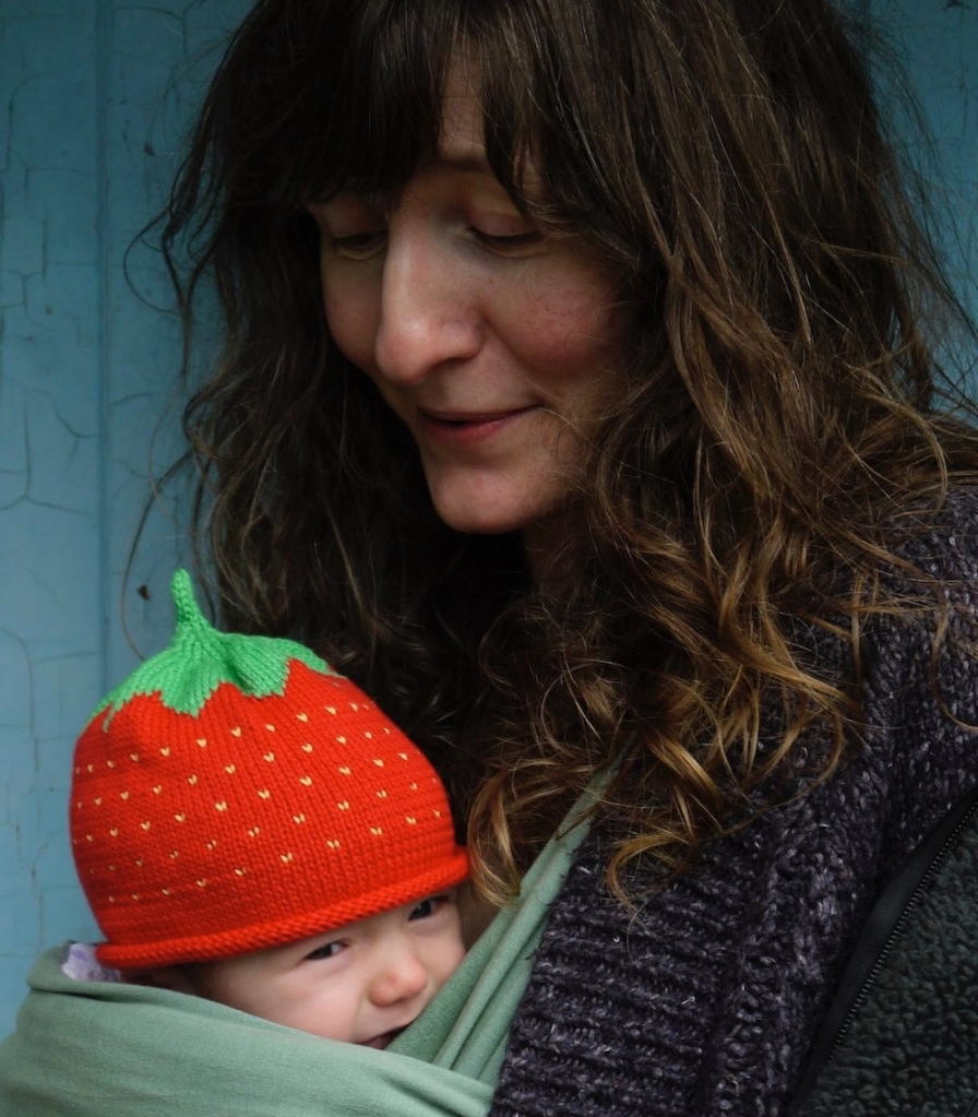 Ali with long flowing brown hair and her baby in a sling with a strawberry hat