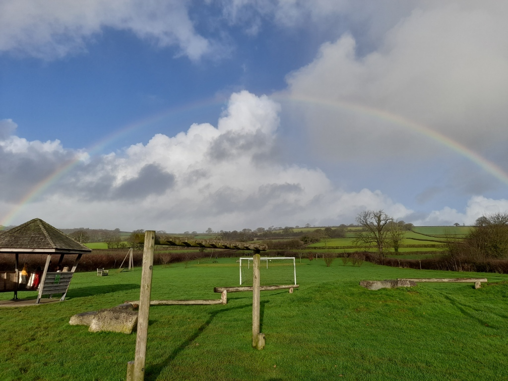 Rainbow over a field with play equipment