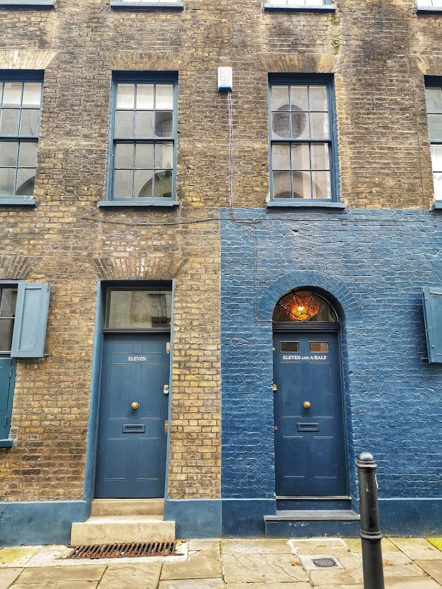 Brown brick building next to a building painted navy blue