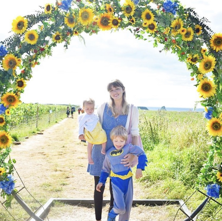 Wendy and two of her kids in a circle of sunflowers