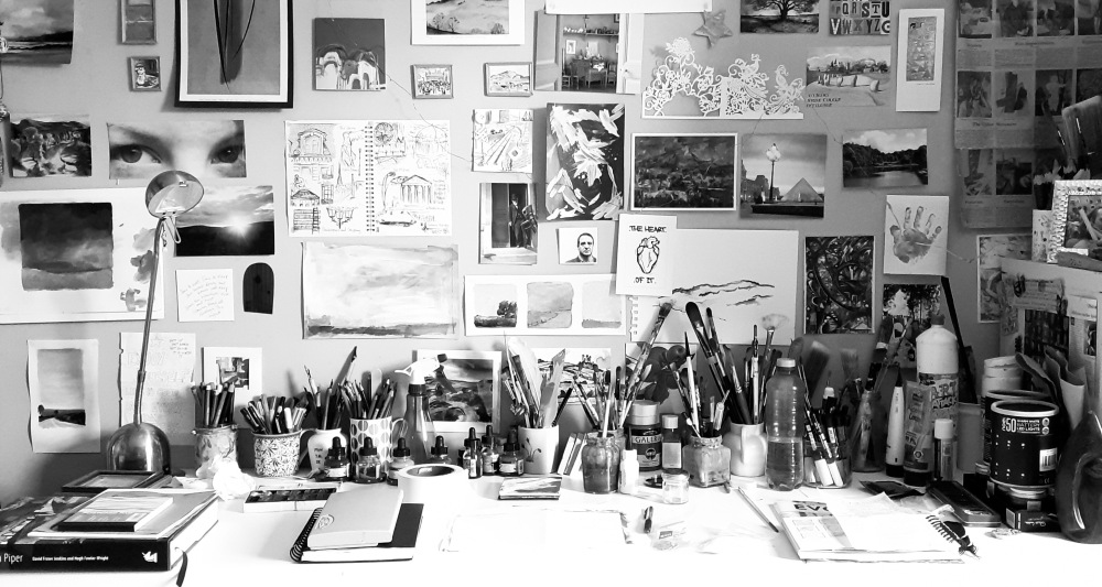 A black and white photo of an artist's desk with several paintings and paint brushes