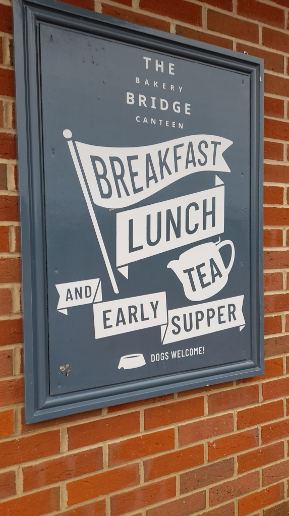 A grey sign with white writing saying breakfast, lunch, tea and early supper
