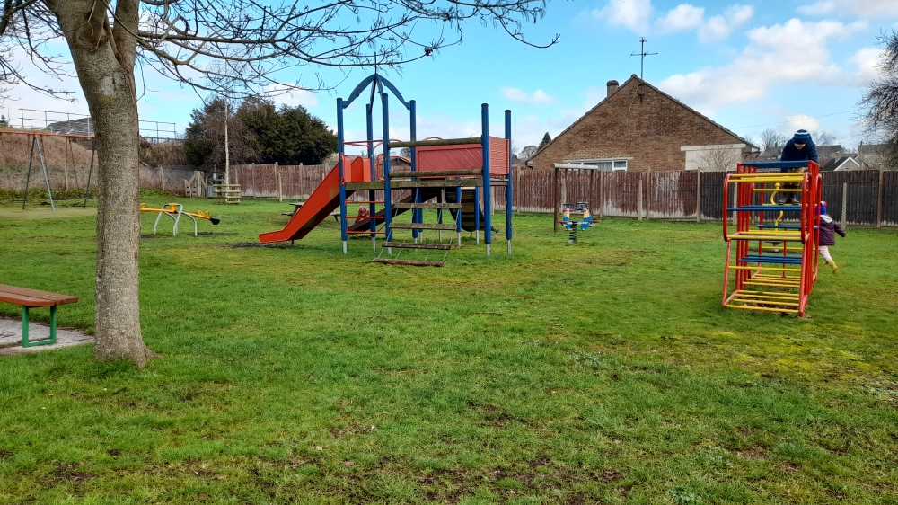 Primary coloured climbing frame with slide and another climbing frame too railway line just visible in the top left