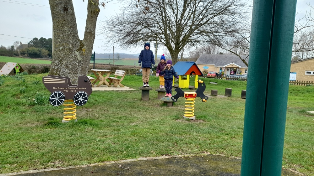 A playpark with three kids standing on tree stumps looking rather like meerkats amongst the colourful play equipment and daffodils