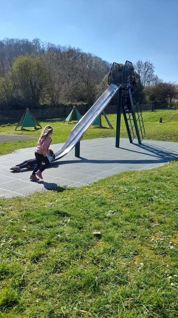 A slide in the foreground with a little girl running towards it in the background is a hill with St Michaels Tower