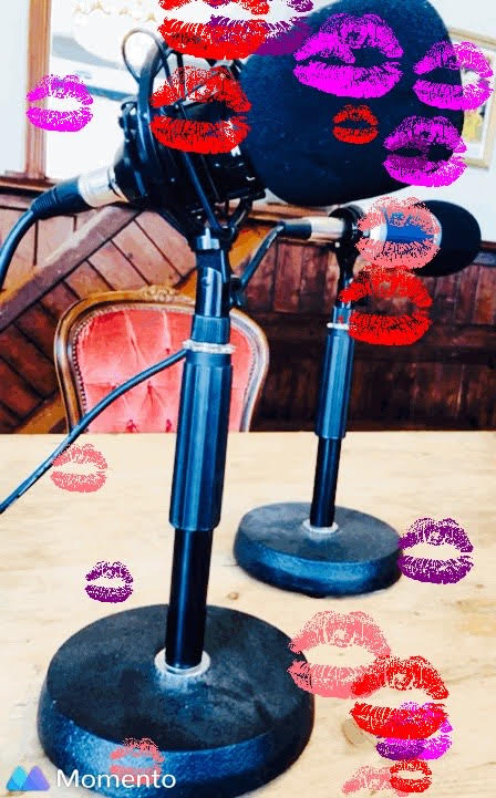 A couple of black microphones in stands on a table with lots of lipstick marks in different pink and purple hues all over the photo