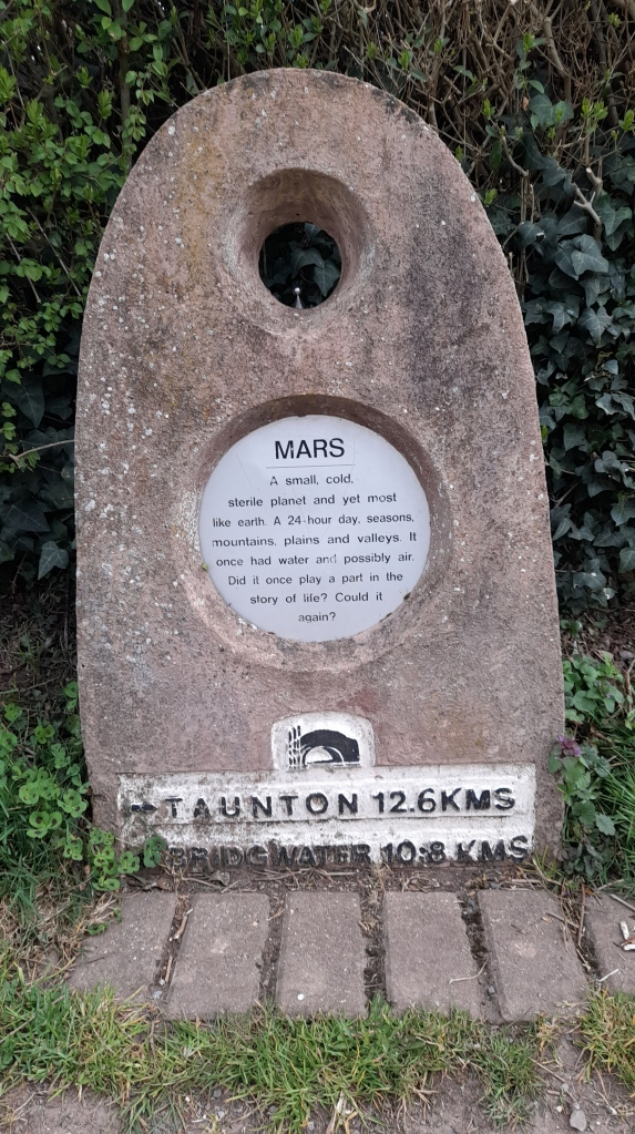 A marker stone with a small metal planet. It reads: Mars. A small, cold sterile planet and yet most like earth. It has 24 hour days, seasons, plains and valleys. It one had water and possibly air. Did it once play a part in the story of life? Could it again? Taunton 12.6 kms Bridgwater 10.8 kms.