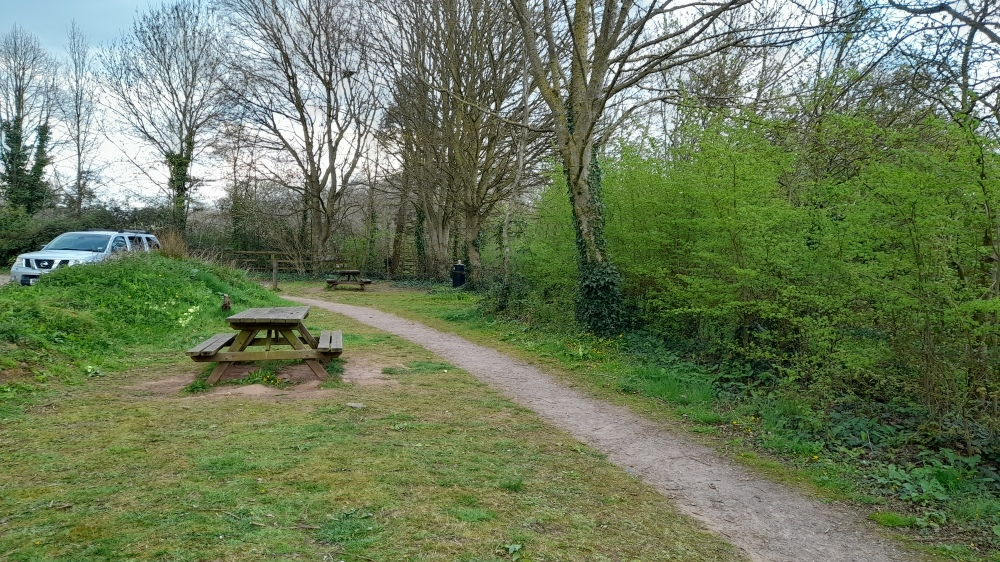 A picnic bench on a grassy bank on the edge of a car park