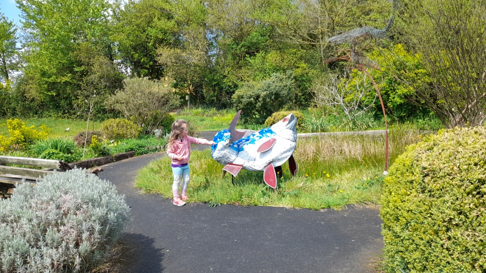 A little girl stood by a large fish sculpture made from recycled materials by a pond