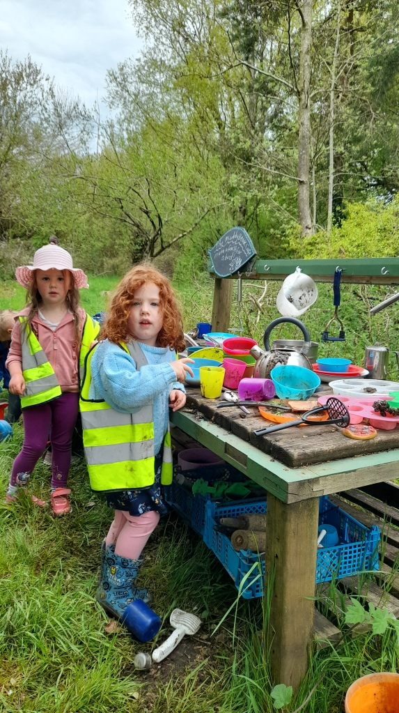 Two little girls one with light brown hair and one with ginger curls playing in the mud kitchen