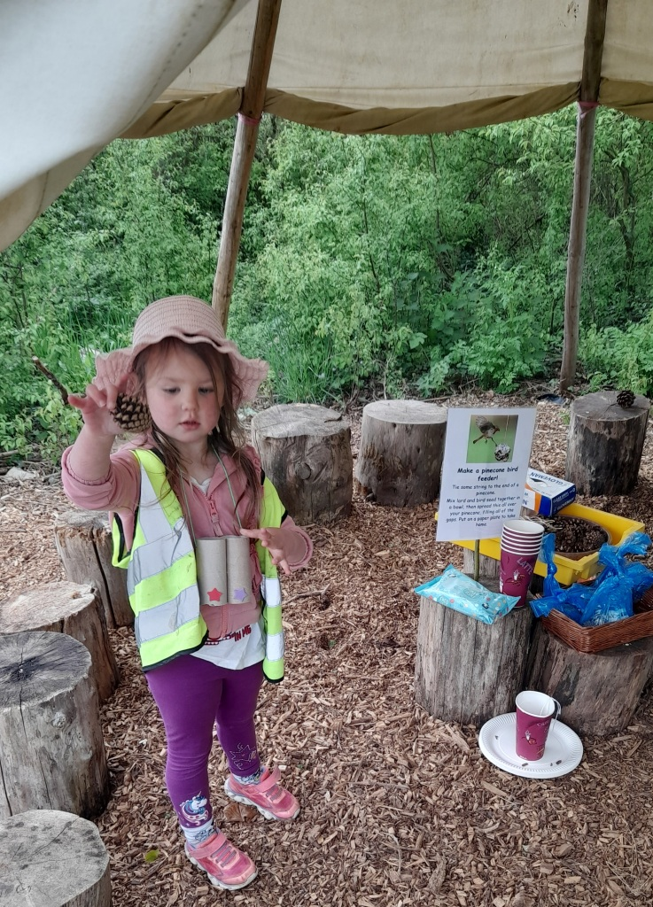 A little girl standing under a tent in the woodland making a bird feeder from seeds and lard